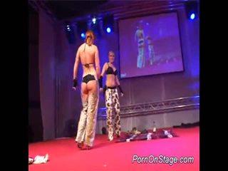 2 meisjes binnenin lesbie showcase met publiek
