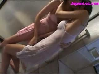 2 flickor i våt clothes kysser patting enligt den dusch