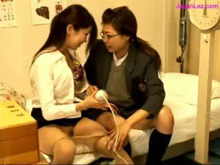 Schoolmeisje en dokter stimulating kutjes met vibrator op de bed in de schoolhospital