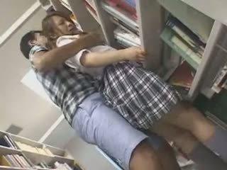 Kautrīga skolniece sagrupētas un used uz a bibliotēka