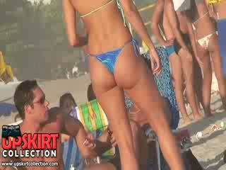 The sexy amateur is staying on the beach letting sun rays pet her adorable bikini ass
