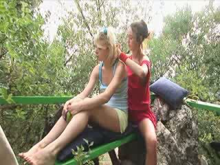 Blonde lesbian friens outside on a chair