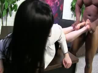Ebony shaft shoots out onto white model feet on couch