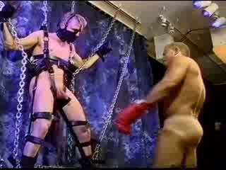 Berambut pirang muscle tiang adalah suspended sebagai dia gets dia buah zakar bashed dan szueezed.
