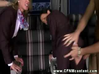 Riietes naine paljaste meestega flight attendants keppimine the passengers