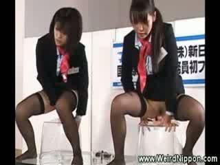 Two एशियन stewardesses है एक सीट पर two vibrators के लिए th crowd